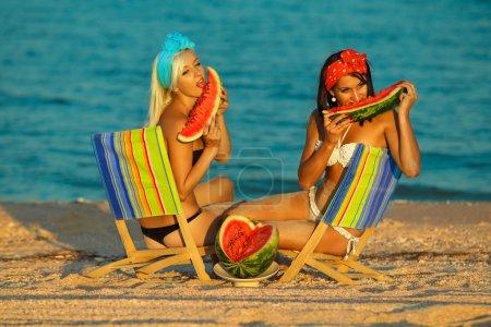 Photo pour Jeunes femmes élégantes en mer avec la pastèque et une boisson relaxante sur la chaise longue - image libre de droit