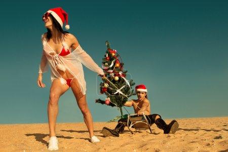 Girl  pulling Santa at the beach