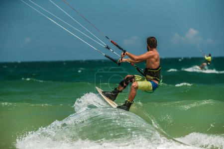 Man Kitesurfing in blue sea
