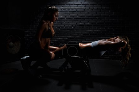 Photo for Woman with personal trainer doing fitness in gym - Royalty Free Image