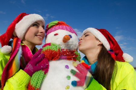 Two young woman kissing a snowman