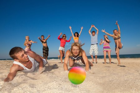 Photo for Group of young joyful people playing volleyball on the beach - Royalty Free Image