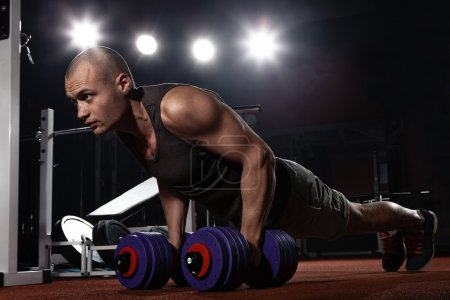 Photo for Muscular young bodybuilder pushing up on floor - Royalty Free Image