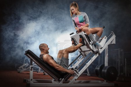 Photo for Man weightlifter doing legs presses with his trainer up on simulato - Royalty Free Image