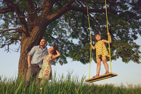 Girl on  swing with parents