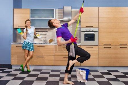 Photo pour Cuisine moderne - femme avec une éponge et souriant jeune homme nettoyage du sol à la maison et faire semblant de chanter la chanson avec mop - image libre de droit