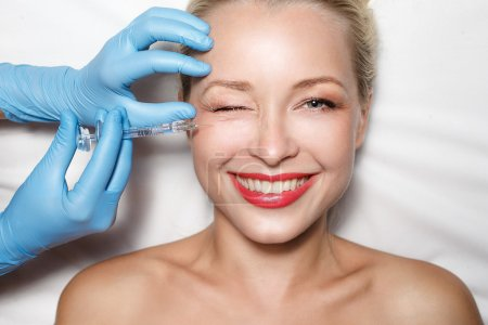 Photo for Plastic Surgery Concept. Attractive woman at plastic surgery with syringe in her face - Royalty Free Image