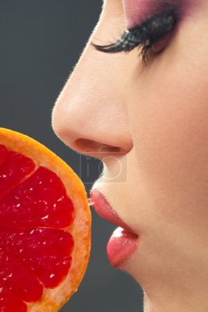 Profile of female face with pummelo slice over dar...
