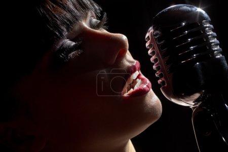 Photo pour Une chanteuse devant un micro. Isolé sur un fond noir - image libre de droit