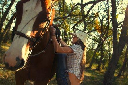 Photo pour Belle fille chevauchant un cheval dans le jardin - image libre de droit