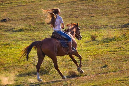 Woman in blue jeans riding a horse
