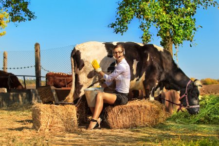 Businesswoman  milking cow on farm
