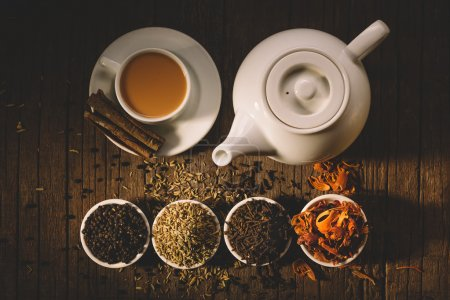 Photo for Teapot and cup of hot tea with milk and cinnamon sticks, different sorts of dry tea in bowls top view - Royalty Free Image