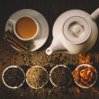 Teapot and cup of hot tea with milk and cinnamon sticks, different sorts of dry tea in bowls top view
