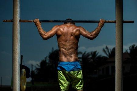 Athlete doing pull-up on horizontal bar