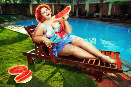 overweight woman eating watermelon by the pool