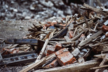 A closeup image of a garbage dump with ruined brick and wooden p