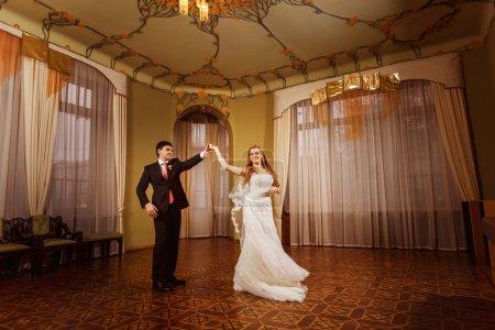 Photo pour Danse de mariage d'un beau couple de mariage dans un magnifique hall vintage spacieux avec parquet en bois et plafond à motifs . - image libre de droit