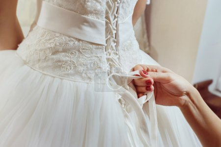 A closeup image of wedding preparations. Bridesmaid is helping put bride elegant luxury dress.