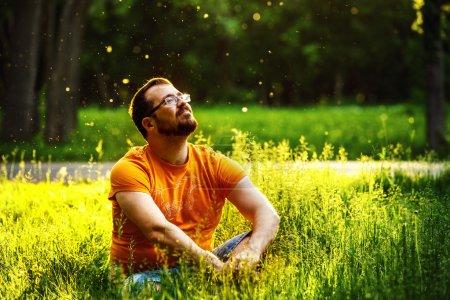 Photo pour Un homme heureux rêveur réfléchie est assis sur l'herbe verte dans un parc à la journée d'été ensoleillée et avenir. Concept de relaxation, bien-être, mode de vie. - image libre de droit