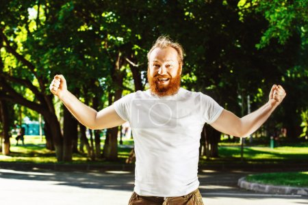 Happy man with red beard is putting hands up as gesture of success, achievement at green summer park background.