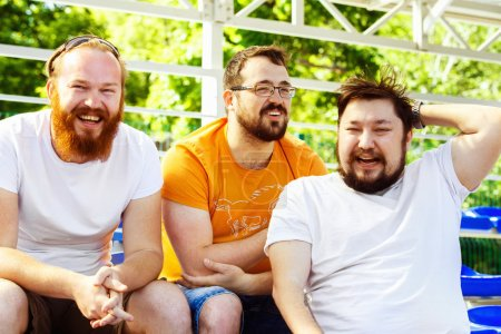 Photo pour Trois jeunes amis joyeux parlent et rient à l'arrière-plan du stade de jour d'été . - image libre de droit