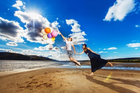 Happy young pair with bright balloons is having fun jumping at summer beach background.