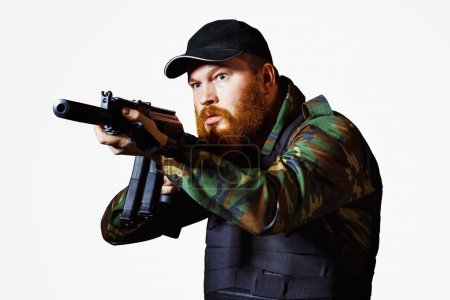 Terrorist in camouflage with red beard and cruel face is holding rifle isolated at white background.