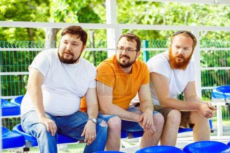 Photo pour Trois jeunes amis sérieux regardent un match de football au stade d'été . - image libre de droit