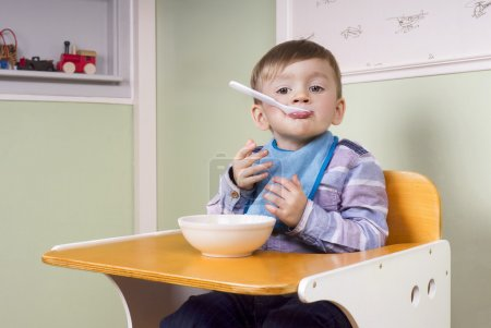 Foto de Two year old boy sitting in his chair eating yoghurt and making fun - Imagen libre de derechos