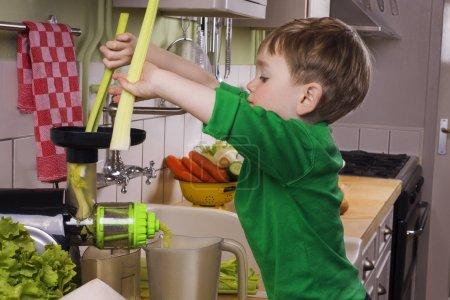 Little boy making green juice