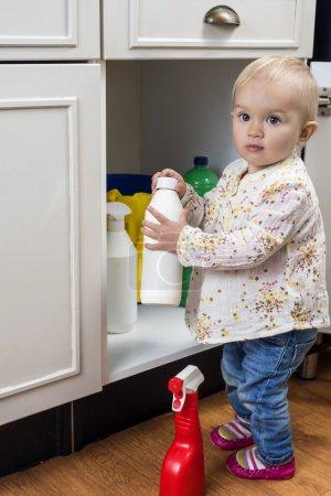 Photo pour Petit enfant jouer avec des produits à la maison de nettoyage - image libre de droit