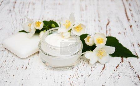 Photo pour Crème hydratante pour le visage et le corps aux fleurs de jasmin sur fond de bois blanc - image libre de droit