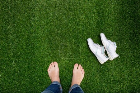 Photo for Feet resting on green grass with slying sneakers - Royalty Free Image