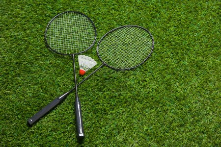 Crossed badminton rackets lying on the grass