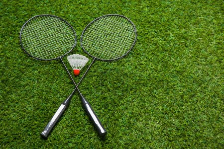 Photo pour Raquettes de badminton allongées sur de l'herbe verte pour une vie active - image libre de droit