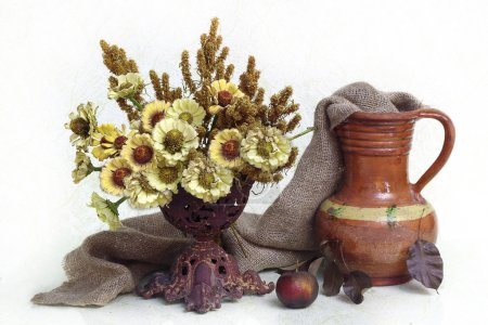 Yellow flowers in a vase and a jug from clay on a white background.