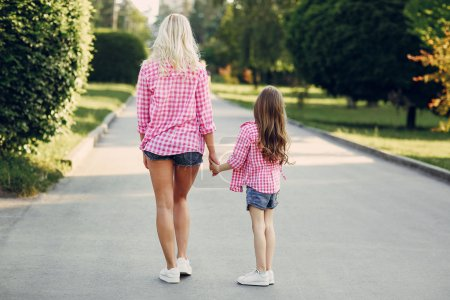 Photo for Mom and daughter walk in the Park shirts - Royalty Free Image