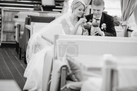 Wedding couple sitting in a cafe on their wedding ...