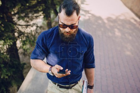 Photo for Stylish bearded man walking on a city map and use gadgets - Royalty Free Image