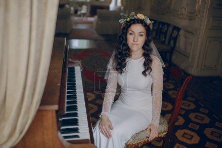 Photo pour Charmant couple de mariage jouant sur un vieux piano dans la chambre - image libre de droit