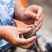 Workers producing handmade art vase earthenware at market.