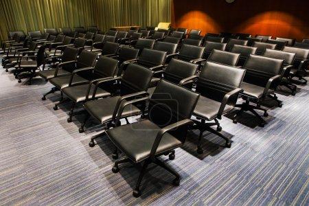 Photo pour Chaises noires dans la salle de réunion - image libre de droit