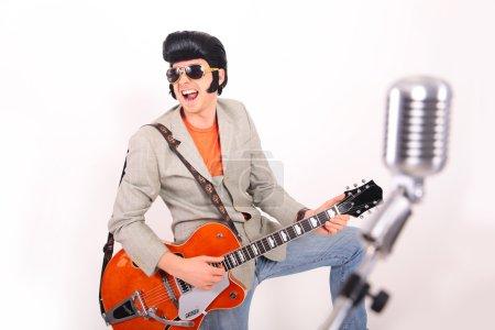 Elvis Presley plays guitar and
