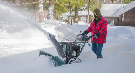 Photo pour Un Canadien portant des vêtements de travail d'hiver, conduisant une machine à jeter de la neige un jour d'hiver après qu'une tempête de neige ait déversé 8 (8) pouces de neige . - image libre de droit