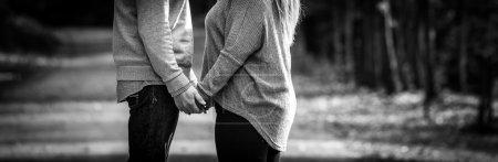 Photo pour Un jeune couple plein d'espoir, main dans la main, chacun d'eux pendant l'arrêt à l'extérieur lors d'une promenade le long d'une route de campagne. - image libre de droit