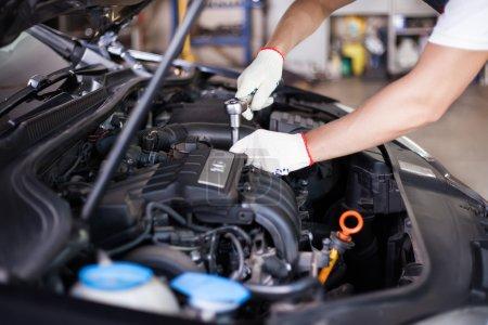 Photo pour Mains de mécanicien automobile dans le service de réparation automobile. - image libre de droit