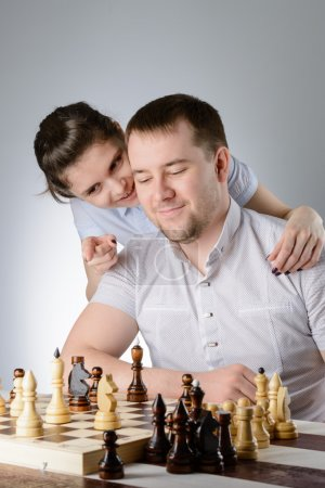 Woman helps a man to play chess