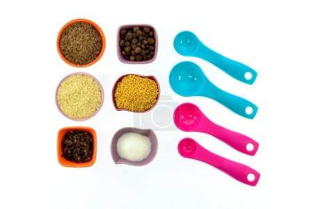 Seeds, spices, grains in small multi-colored cups and measuring spoons