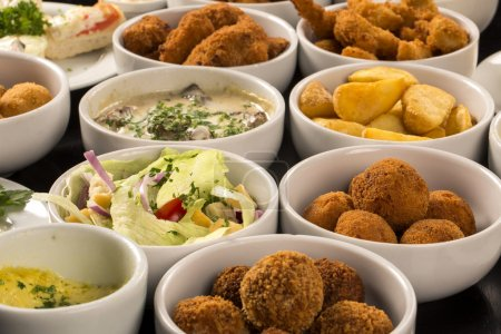 Mixed brazilian snacks, including pastries, fried chicken, salad